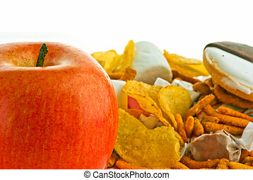 Apple and junk food - A apple and a lot of junk food on...