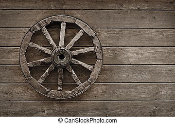 Old wagon wheel on wooden wall - An old wooden wagon wheel...