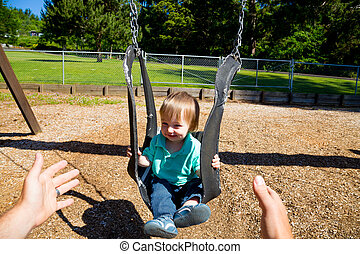 Boy on Swing Set - A father pushes his son on a unique...