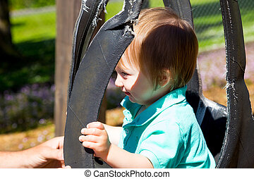 Boy on Swing Set - A cute young boy sits on a swing set and...