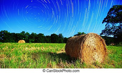 Farmland and Stars - Moonlit hay bale under star trails on a...