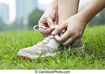 Tying sports shoe - female athlete tying running shoes