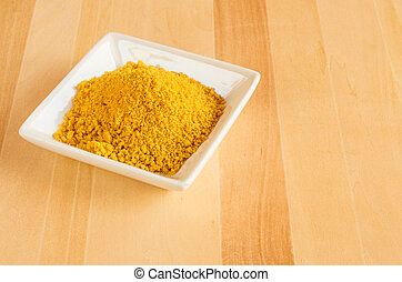 Dish of tumeric spice for use in cooking - A white plate of...