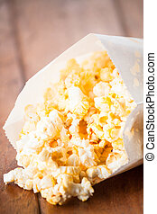 Fresh popcorn in paper bag on wood table