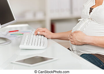 Pregnant Woman With Hand On Belly Using Computer At Table -...