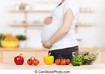 Vegetables With Pregnant Woman In Background - Closeup of...