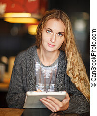 Woman with touch screen tablet computer in cafe