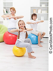 Gymnastic exercise with the kids - Woman doing gymnastic...