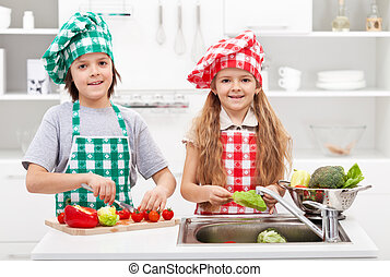 Kids helping in the kitchen - washing and slicing vegetables...