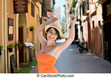 Sexy woman wearing hat and raising her hands in the air