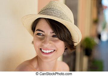 Trendy female - Smiling trendy female wearing hat looking at...