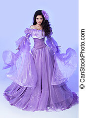 Fashion young magnificent woman in violet blowing dress. Studio photo