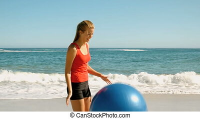 Woman playing with her fitness ball on the beach in slow...