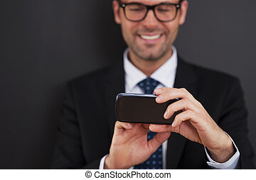 Businessman texting on smart phone