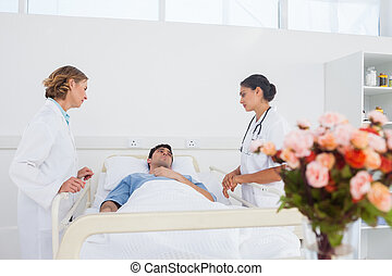Lying patient in his bed looking to his doctors