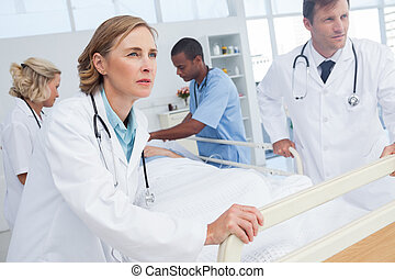 Doctors about to walk with patient bed