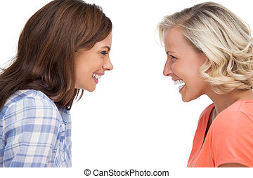 Two friends looking to each other and laughing on white...