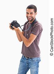 Stylish man holding camera and smiling on white background