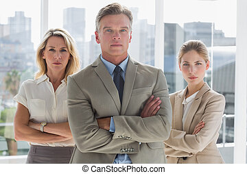 Three business people standing together in a modern office
