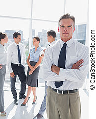 Boss standing with arms folded in a modern office with...