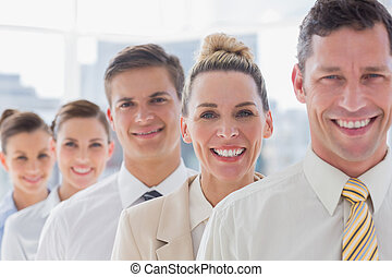 Smiling handsome businessman standing with his team