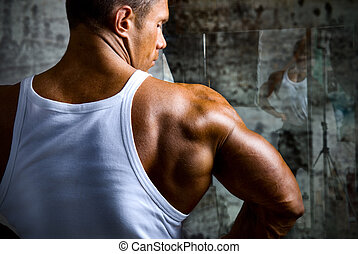 A beautiful young muscular man's shoulder. Bodybuilder on...