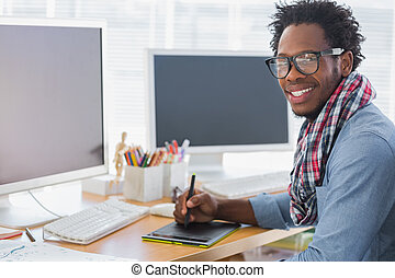 Smiling graphic designer using a graphics tablet in a modern...