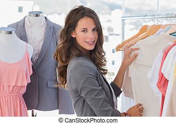 Fashion woman choosing clothes and looking at the camera