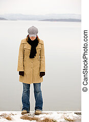 Shy Winter Woman - A young woman standing by the ocean in...