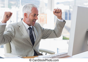 Businessman cheering at his desk looking at computer