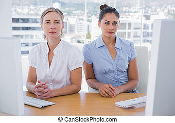 Serious businesswomen sitting side by side at a desk in the...