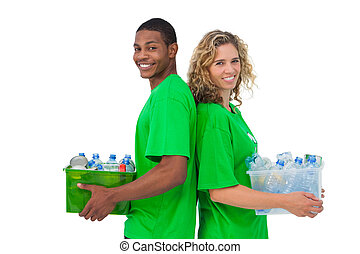 Cheerful environmental activists holding box of recyclables...