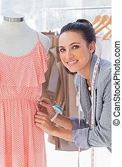 Attractive fashion designer adjusting dress