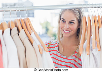 Pretty woman looking at clothes in a clothing store