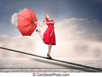 Pretty woman with a broken umbrella over the clouds standing...