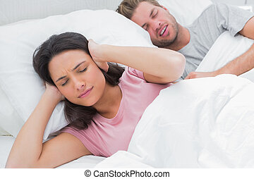 Woman covering ears while her husband is snoring next to her