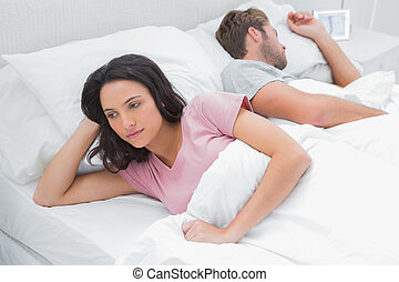Woman thinking in her bed next to her sleeping husband