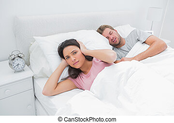 Snoring man is annoying his wife who tries to sleep in her...
