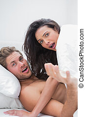 Couple surprised in their bed - Embarrassed couple surprised...