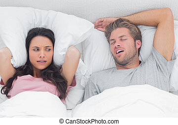 Pretty woman annoyed by the snoring of her husband in bed