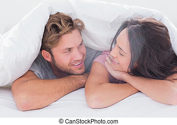 Couple under quilt smiling to each other