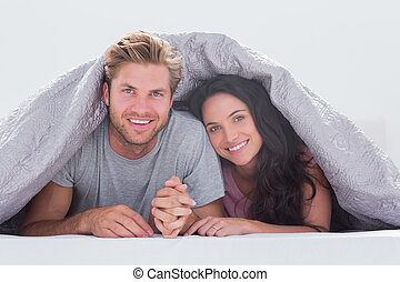 Cheerful couple under the cover in their bed