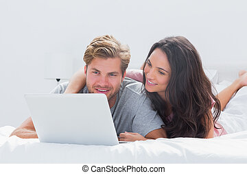 Woman embracing husband while using a laptop in bed