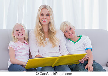 Portrait of a mother reading a story to children on couch