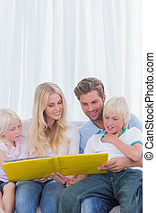 Cheerful family reading a story together on the couch