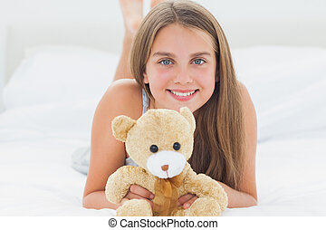 Cute young girl holding a teddy bear while she is lying on...
