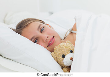 Cheerful girl relaxing with her teddy bear in the bed
