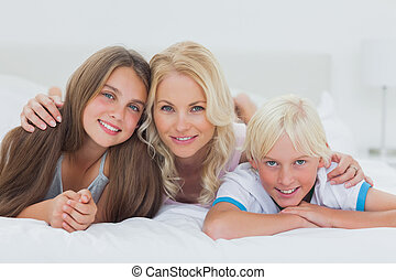 Cheerful siblings and mother lying on bed