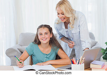 Smiling mother and daughter doing homework