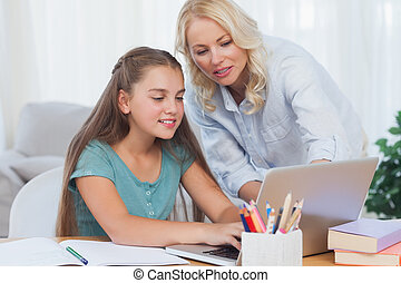 Mother helping her daughter to do homework